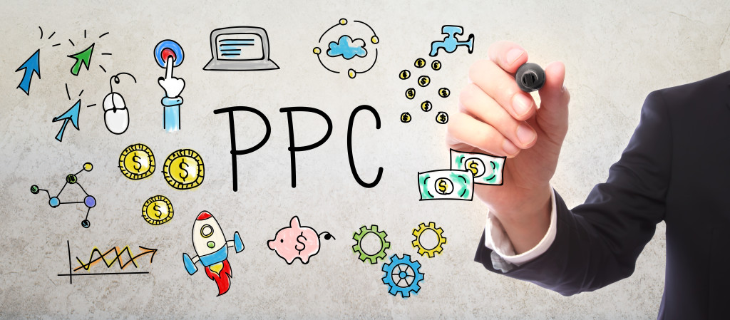 Businessman drawing PPC - Pay Per Click concept with a marker